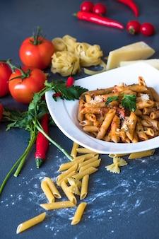 Teigwaren mit tomatensauce, knoblauch, paprikapfeffer, getrockneten tomaten, petersilie, parmesan auf weißem teller