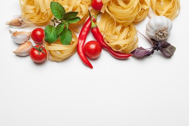 Teigwaren-spaghettis mit bestandteilen für das kochen von teigwaren auf einem weißen hintergrund, draufsicht.