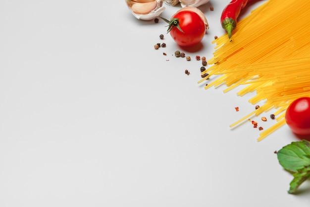 Teigwaren-spaghettis mit bestandteilen für das kochen von teigwaren auf einem weißen hintergrund