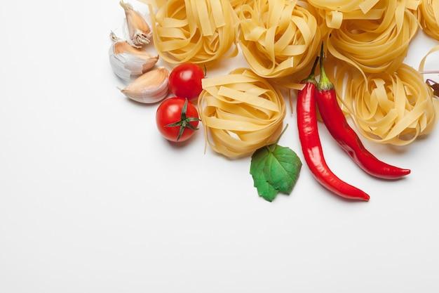 Teigwaren-spaghettis mit bestandteilen für das kochen von teigwaren auf weiß