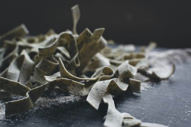 Teigwarenbandnudeln bedeckt durch mehl auf einem schwarzen hintergrund
