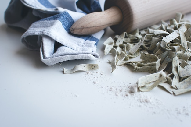 Teigwarenbandnudeln bedeckt durch mehl mit einer hölzernen rolle auf einem weißen hintergrund