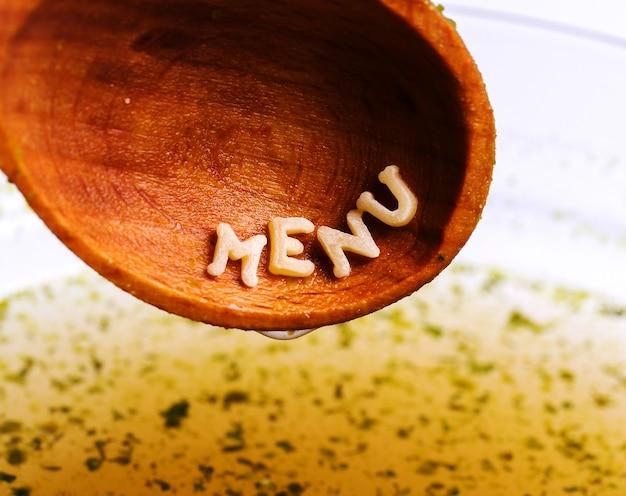 Teigwarenbuchstaben mit menüwort auf hölzernem löffel
