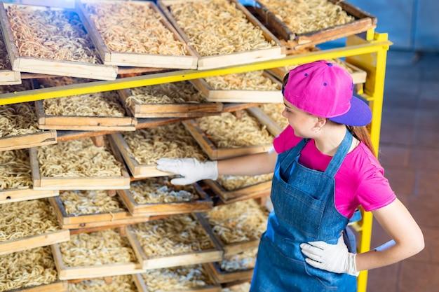 Teigwarenfabrik herstellung von mehlprodukten. technologische herstellung von makkaroni. fabrikindustriearbeit, rohe makkaroni-nahaufnahme.
