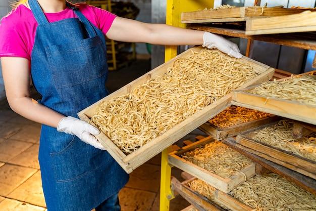 Teigwarenfabrik. herstellung von teigwaren. kraftvolle makkaroni. arbeiter mit holzkiste mit nudeln.