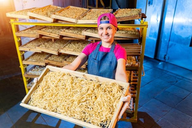 Teigwarenfabrik und teigwarenproduktionsstufen. frische makkaroni in kisten auf regalen geschnitten. industrielle maschine.
