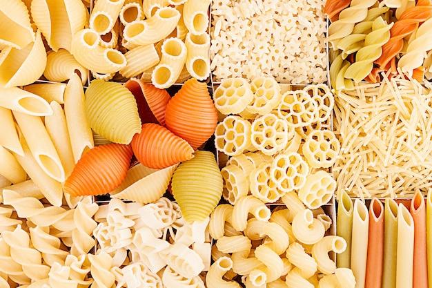 Teigwarenhintergrundzusammenstellung des italienischen makkaronis der verschiedenen arten in den schachzellen