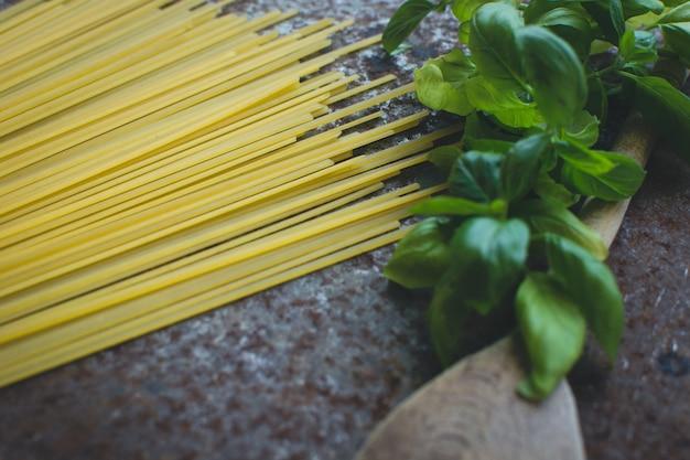 Teigwarenspaghettis mit basilikum und hölzernem löffel auf einem rostigen metallischen hintergrund