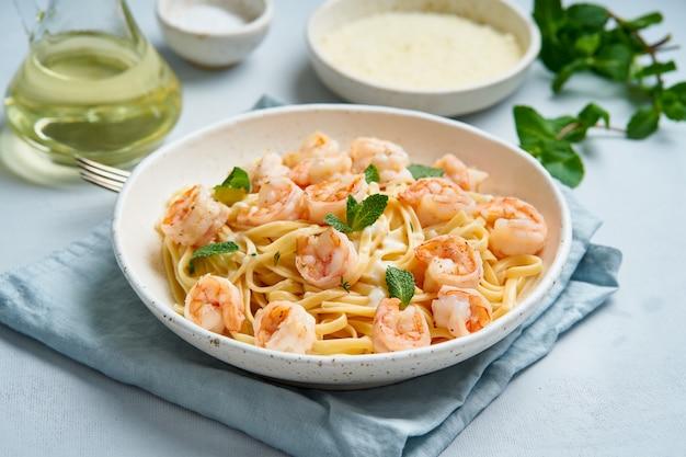 Teigwarenspaghettis mit gegrillten garnelen, bechamelsoße, tadelloses blatt auf blauer tabelle, italienische küche