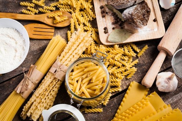 Teigwarenspaghettis mit mehl, ei auf altem hölzernem hintergrund