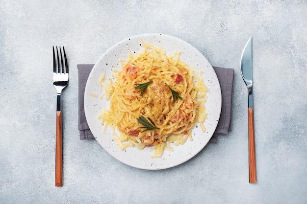 Teigwarenspaghettis mit speckeikäse auf einer platte mit gewürzen. traditionelles italienisches gericht carbonara. grauer betontisch. kopieren sie platz.