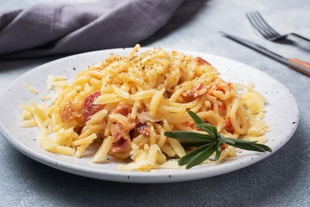 Teigwarenspaghettis mit speckeikäse auf einer platte mit gewürzen. traditionelles italienisches gericht carbonara. grauer betontisch