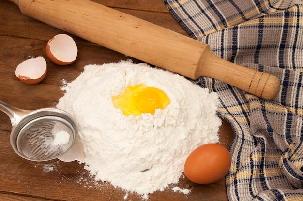 Teigzubereitung backzutaten eier und mehl, sieb und nudelholz auf holzhintergrund