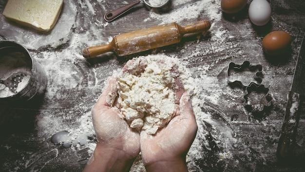 Teigzubereitung. teig frauenhände und werkzeuge. sieb, nudelholz, messer, schneebesen auf holztisch. draufsicht