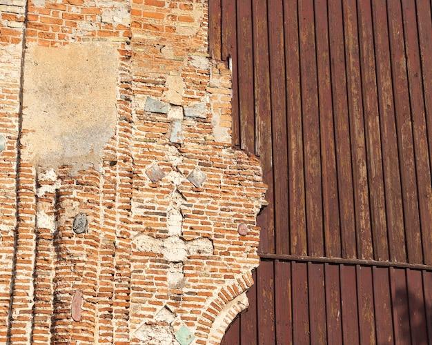 Teil der backsteinmauer eines alten gebäudes, das zerstört und durch ein holzgebäude ersetzt wurde