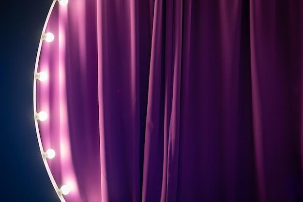 Teil der zone auf der bühne, geschmückt mit lampen. lila hinter der bühne, helle beleuchtung.