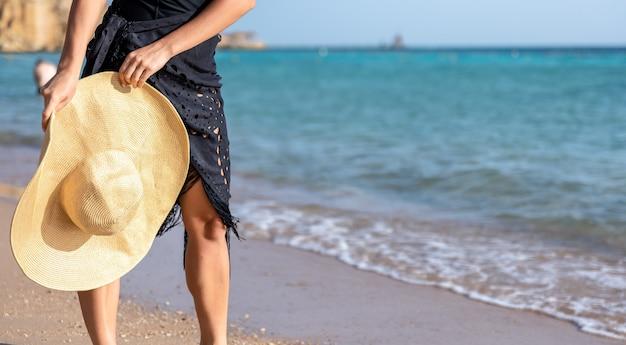 Teil des körpers einer frau, die an einem heißen sommertag an der küste entlang geht.