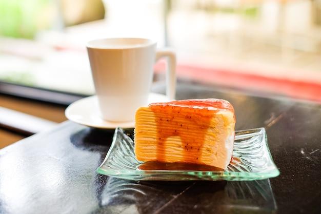 Teil des kreppkuchens, der mit erdbeersoße überstiegen wird, dienen auf klarem teller und heiße frische milch im glas