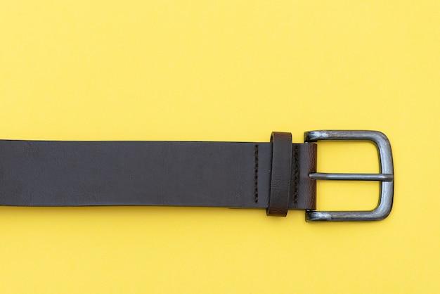 Teil des ledergürtels auf gelbem hintergrund, draufsicht. lässiger kleidungsstil