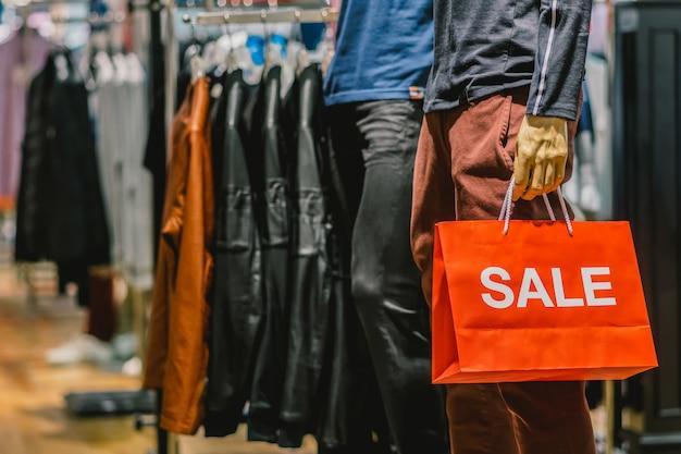Teil des männlichen mannequins kleidete in der zufälligen kleidung an, welche die verkaufspapiereinkaufstasche hält