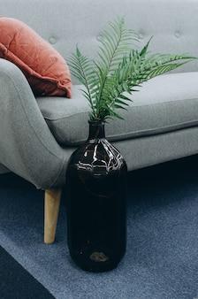 Teil des skandinavischen innenraums mit einem sofa und einem vase mit einer blume