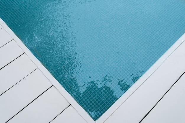 Teil des swimmingpools mit blauem wasser. strahlend blaues wasser im pool. platz für text. hintergrund