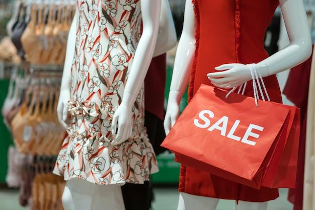 Teil des weiblichen mannequins kleidete in der zufälligen kleidung an, welche die verkaufspapiereinkaufstasche hält