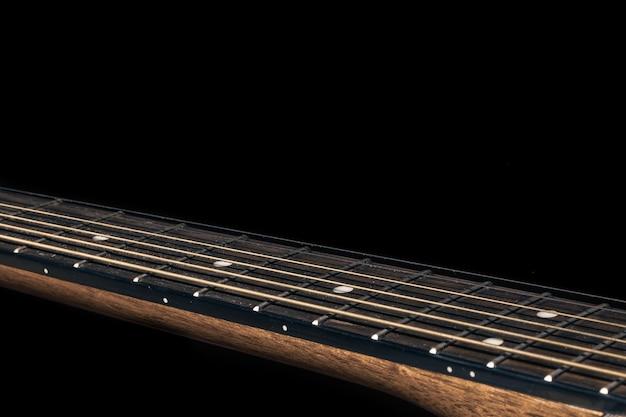 Teil einer akustikgitarre, gitarrengriffbrett auf schwarzem hintergrund.