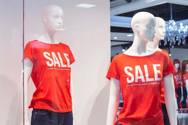 Teil einer weiblichen schaufensterpuppe in freizeitkleidung mit dem textverkauf in einem einkaufskaufhaus für einkaufs-, mode- und werbekonzepte.