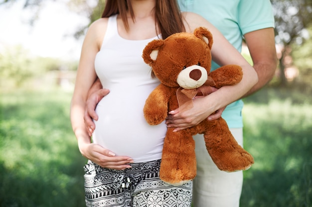 Teil zukünftiger eltern mit teddybär