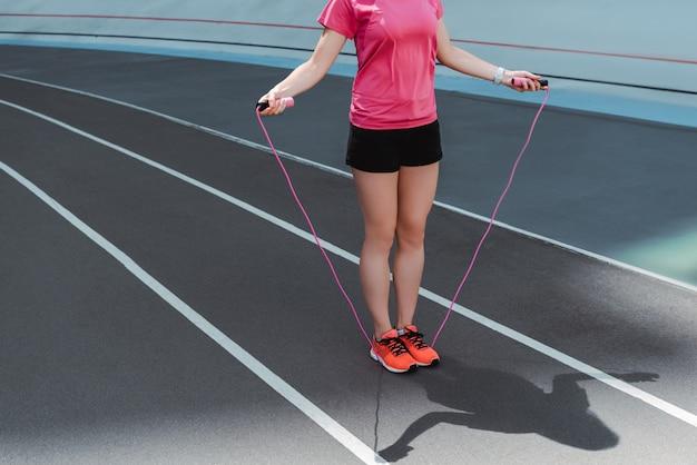 Teilansicht der sportlerin in turnschuhen, die springseil auf laufbahn halten