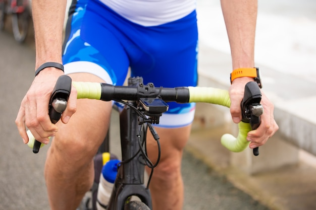 Teilansicht des mannes, der fahrrad nahe meer reitet