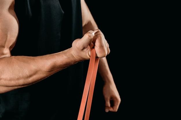 Teilansicht des muskel-bodybuilder-trainings mit auf schwarz isoliertem widerstandsband