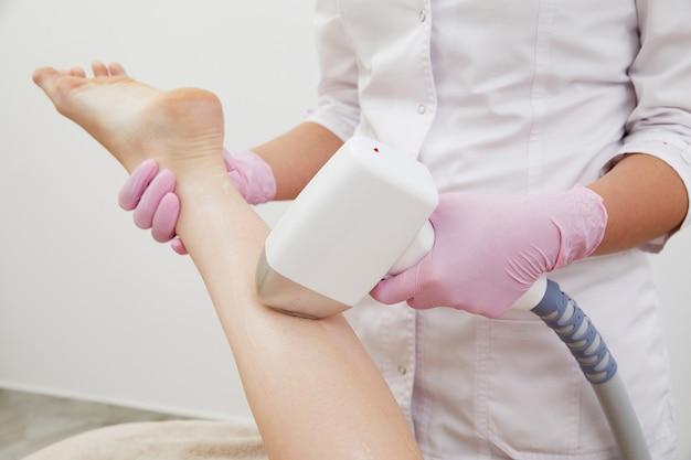 Teilansicht einer frau, die in einem salon eine laser-haarentfernungs-epilation am bein erhält