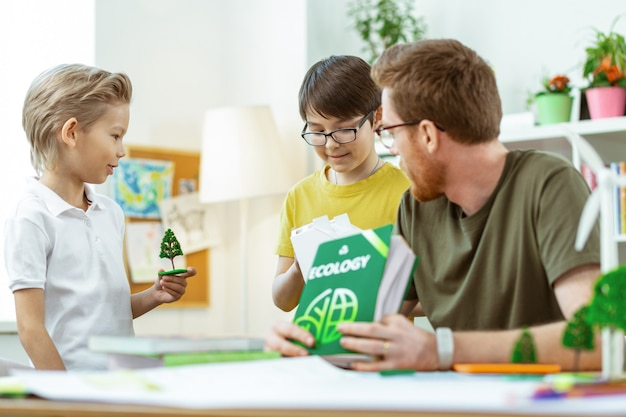 Teile des modells. blonder junger student im weißen t-shirt mit plastikbaum, während sein freund das weiße haus beobachtet
