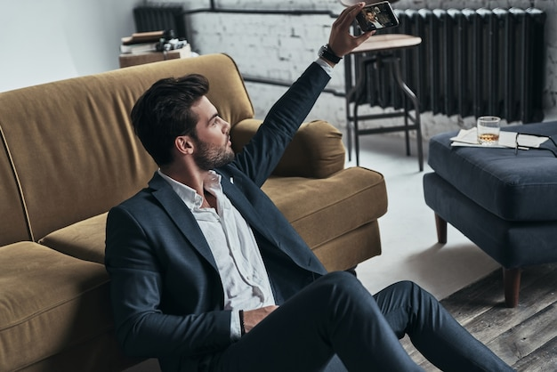 Teilen seiner fotos. hübscher junger mann in vollem anzug, der ein selfie macht, während er zu hause auf dem boden sitzt