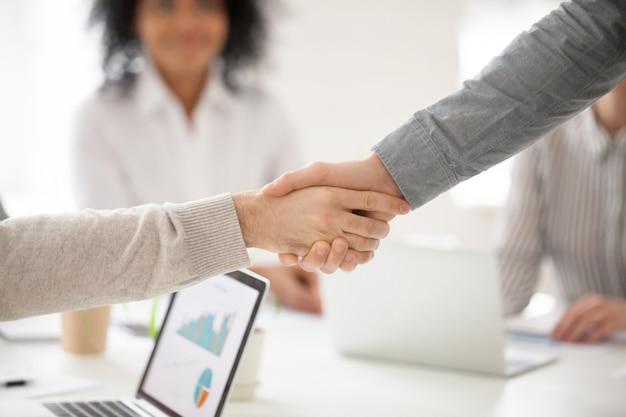 Teilhaberhändeschütteln bei der gruppensitzung, die projektinvestition, nahaufnahme macht