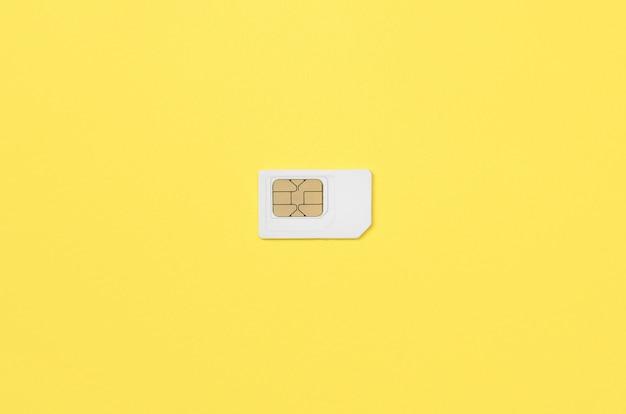 Teilnehmeridentitätsmodul. weiße sim-karte auf gelbem hintergrund