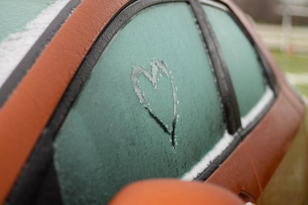 Teilweise verschwommenes herz gezeichnet mit einem finger auf das gefrorene fenster eines orangefarbenen autos im winter, selektiver fokus, kopierraum