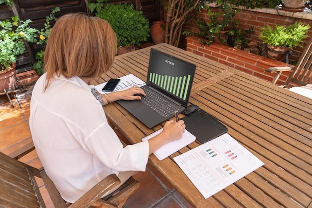 Telearbeit der frau in ihrem hausgarten mit dokumenten und laptop