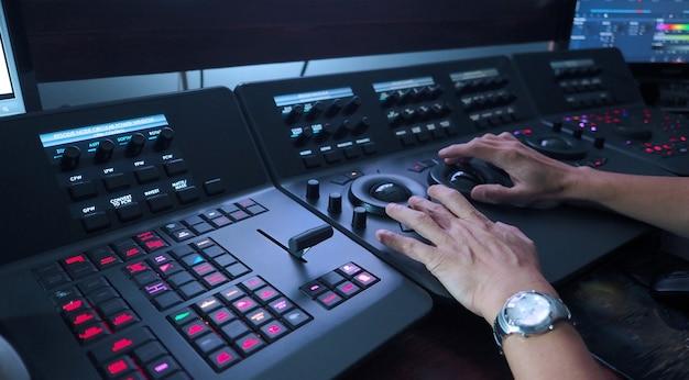 Telecine-controller-maschine und menschenhand, die die farbe eines digitalen videofilms oder -films bearbeiten oder anpassen