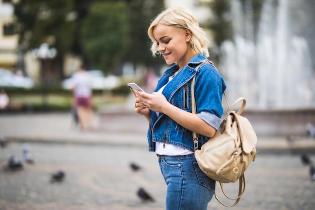 Telefon der jungen blonden mädchenfrau in ihren händen auf straßenwegquadrat-fontain, gekleidet in blue jeans suite mit tasche auf ihrer schulter in sonnigem tag