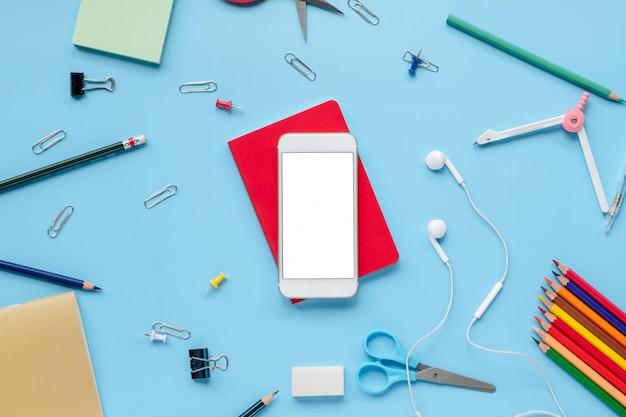 Telefon des leeren bildschirms mit schulbedarfausrüstung auf blauer rückwand flachlage mit kopienbadekurort