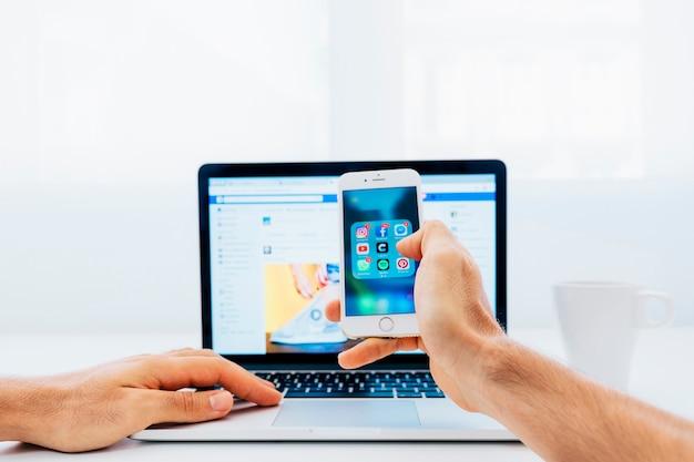 Telefon im vordergrund und blured laptop