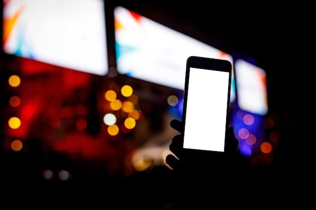 Telefon in den händen des fans in der show. leerer bildschirm