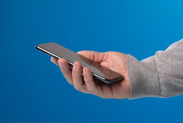 Telefon in den händen des mannes mit grauem pullover