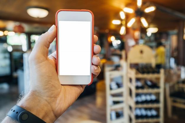 Telefon in der hand eines mannes in einem roten rahmen, in einem geschäft mit warmem licht und regalen mit lebensmitteln. konzept der produktauswahl in der online-bewerbung.