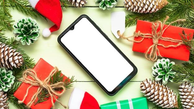 Telefon in einer weihnachtskomposition mit zapfen und geschenken.