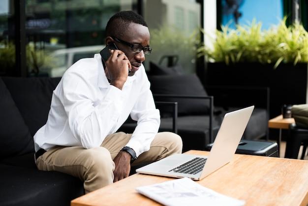 Telefon laptop afrikanische afrikanische abstammung geschäftsperson