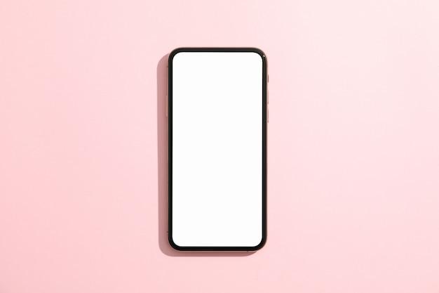 Telefon mit leerem bildschirm auf rosa oberfläche